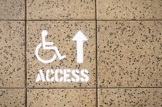A stenciled sign for wheelchair access ahead.