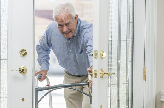 A senior man in his 70s using a walker, coming home through his front door. He is opening the door and stepping into the house.