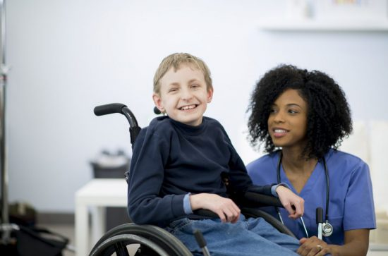 A nurse is with a child in the hospital that has cerebral palsy. The little boy is sitting in a wheelchair. He is smiling and looking at the camera.