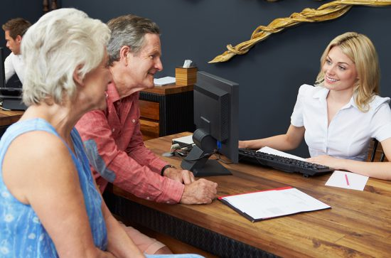 Hotel Receptionist Helping Senior Couple To Check In For Holiday