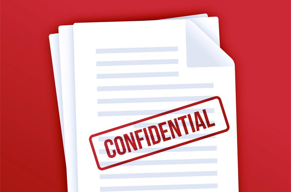 Stack of confidential documents stamped with red confidential stamp to keep them private or secret.